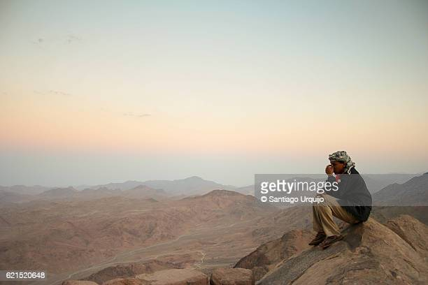 Bedouin watching the sunset from top of Mount Sinai