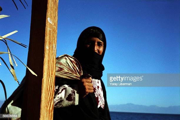 Bedouin woman walks next to a bungalow on January 01 2004 in the Sinai Desert Egypt Weather in the southern desert of Sinai makes it an attractive...