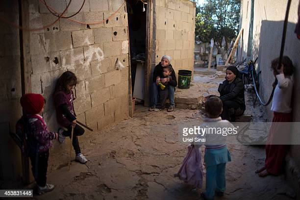 Bedouin women and children of the AlQiyaan tribe spend time aoutside their house on December 5 2013 At the Bedouin village of Umm AlHiran...