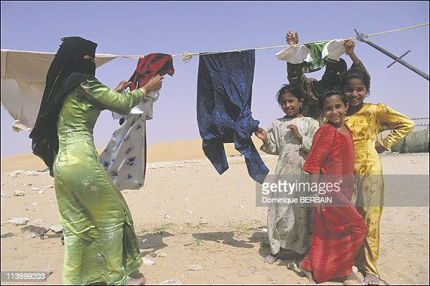 Bedouin women of the Rub al Khali desert the largest desert in Saudi Arabia In February 2003Young Bedouin girls hanging up the laundry They wear...