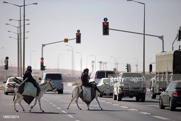 Bedouin women ride their donkeys on October 10 2013 in Be'er Sheva Israel Roughly 200000 Bedouins live in the Negev desert with about half living in...