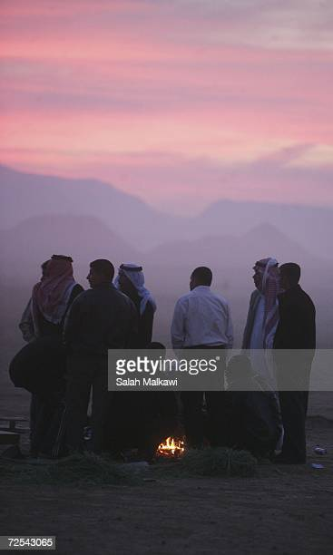 Bedouins gather around a fire while waiting to watch horse riders from the Middle East compete in a 120 km International Endurance Race November 14...