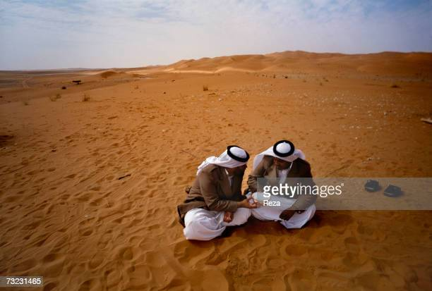 Bedouins of the Yam tribe share a bowl of water on December 2002 in Uruq Bani Ma'arid Reserve Saudi Arabia