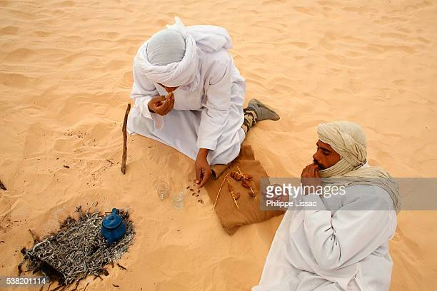 Bedouins sitting by a fire and eating dates in the Sahara