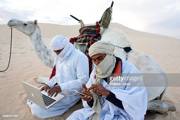 Bedouins using a laptop and a cell phone in the Sahara