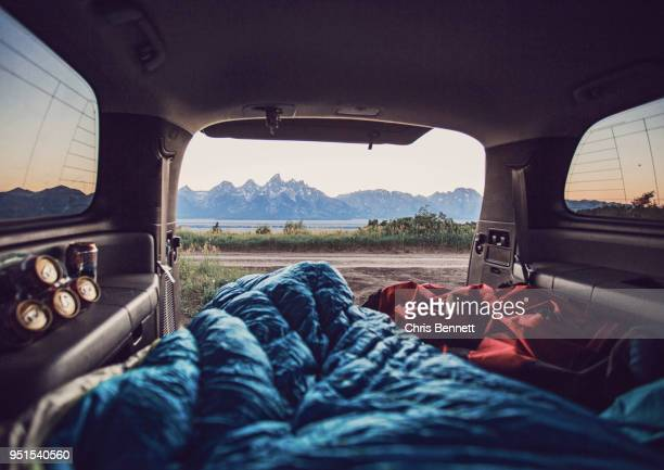 bedrolls inside car with mountain range visible in background, wyoming, usa - boot stock pictures, royalty-free photos & images