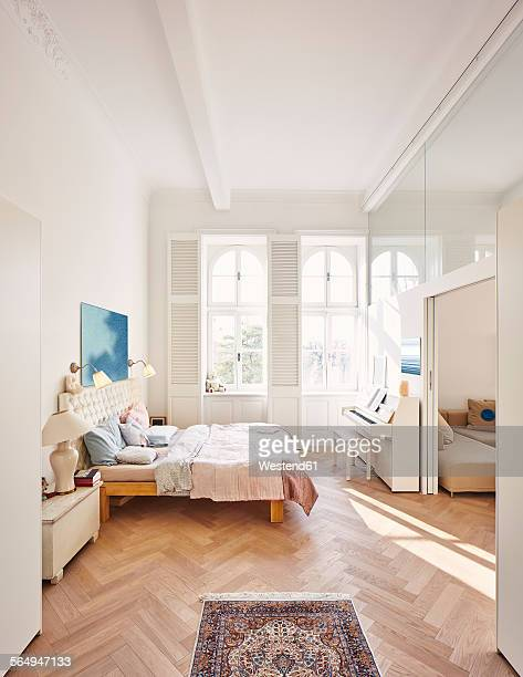bedroom in a refurbished old building with dining table in the foreground - loft stock photos and pictures