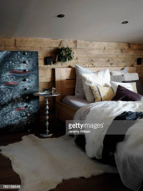 Bedroom interior, wood covered wall behind bed