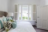 Bedroom window with a garden view in a luxury country house bedroom