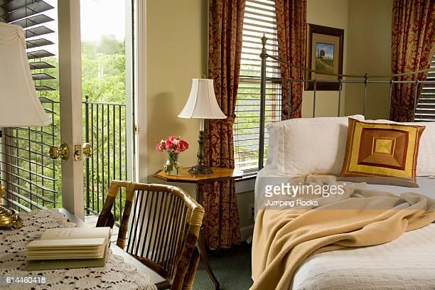 Bedroom with desk next to iron cast bed with open doorway and Venetian blinds