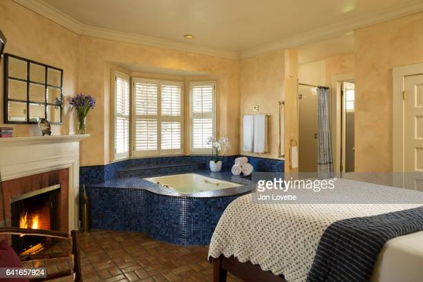bedroom with fireplace and in room tub - inn stock pictures, royalty-free photos & images
