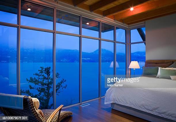 Bedroom with floor to ceiling windows overlooking ocean at dusk