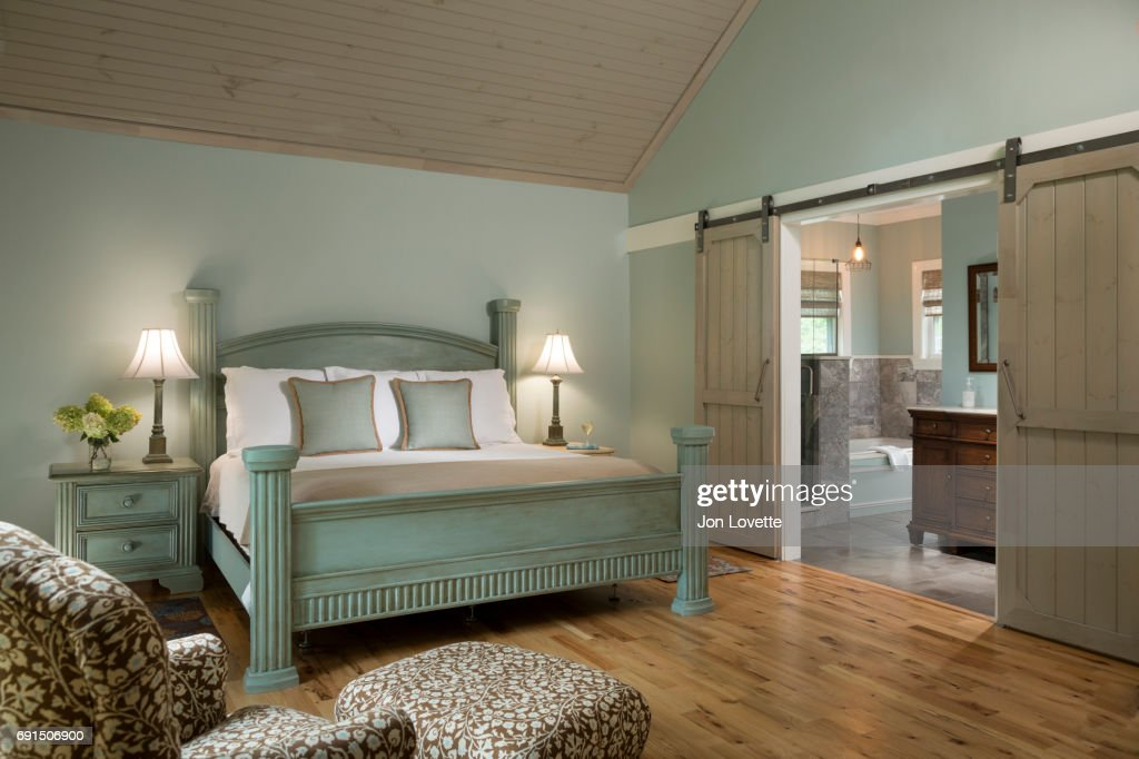 Bedroom With Pale Green Walls High Ceiling And Sliding Door To Bathroom Stock Photo