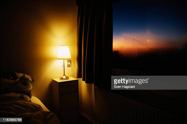 bedside lamp illuminating bedroom corner next to window with view of dusk sky - moody sky stock pictures, royalty-free photos & images