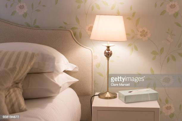 bedside table with light - lamp stock-fotos und bilder