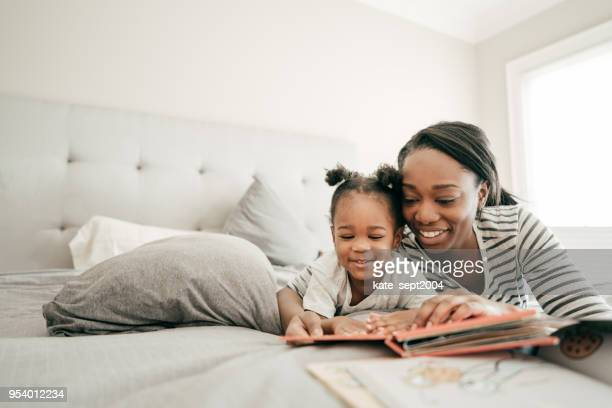 bedtime bonding - african american family home stock photos and pictures