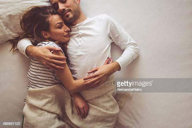 bedtime romance - couple and kiss and bedroom stock photos and pictures