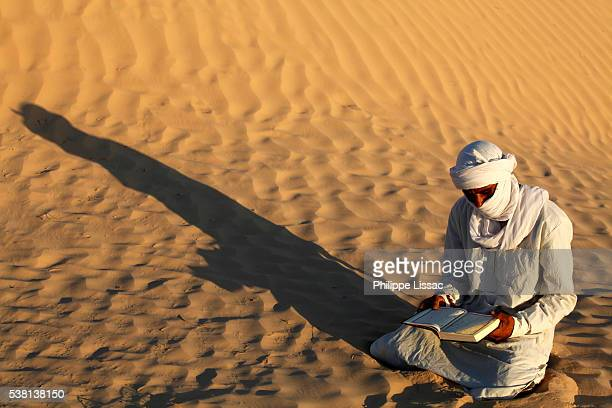 beduin reading the kuran in the sahara - bedouin stock pictures, royalty-free photos & images