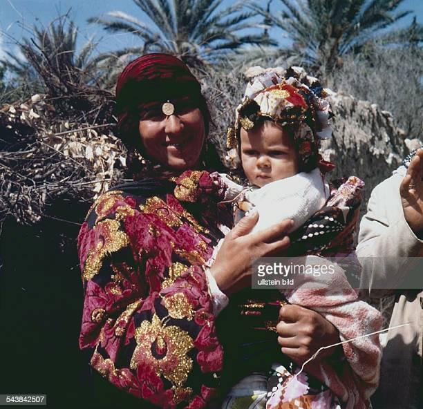 Eine Frau hält ihr mit einer bunten Kopfbedeckung bekleidetes Kind auf ihrem Arm Auch die Beduinin trägt prächtige farbenfrohe Kleidung ihr Kopftuch...