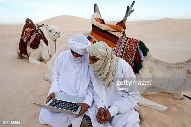 Beduins using a laptop in the Sahara