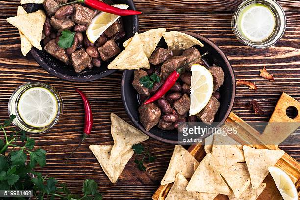 Beef and black bean chili served with corn tortilla chips viewed from above