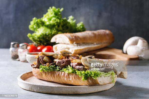 Beef baguette sandwich with champignon mushrooms. Green salad. Fried onion served on ceramic plate with ingredients above over grey blue table. .