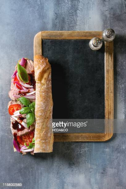 Beef baguette sandwich with tomatoes basil red onion served on empty black chalkboard with salt and pepper over blue texture background Flat lay space