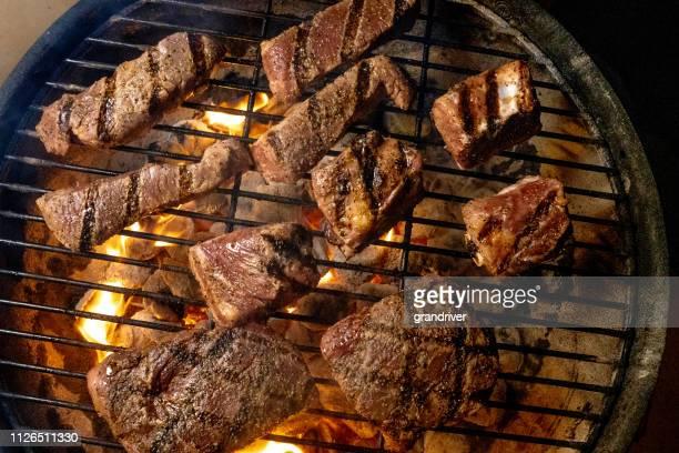 carne de res deshuesada y sin deshuesar las costillas en salsa de barbacoa en una parrilla ardiente - barbeque sauce fotografías e imágenes de stock