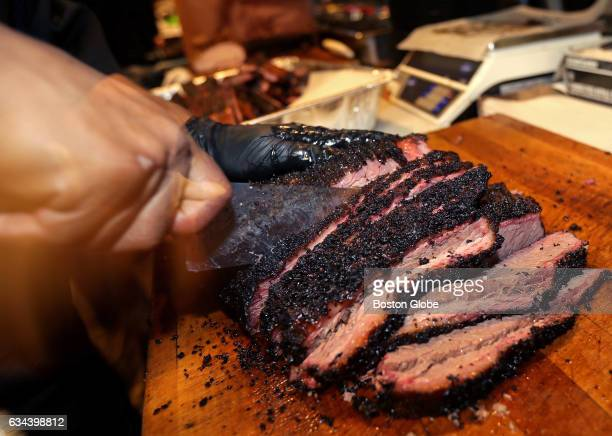 A beef brisket is sliced to order for a customer at Killen's Barbecue on Broadway Street in Pearland TX on Feb 4 2017 Barbecue at Killen's is served...