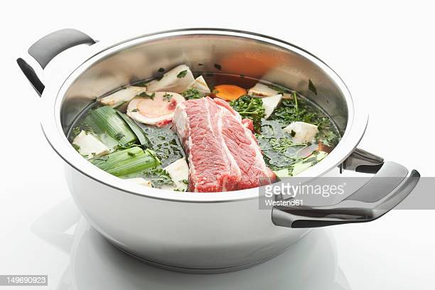 Beef broth ingredient in stew pot on white background