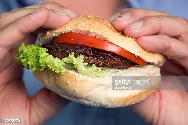 Beef burger created by stem cells harvested from a living cow is held for a photograph by Mark Post, a Dutch scientist, following a Bloomberg...