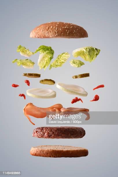 beef burger floating with bacon onion and pickles gray backgroun - flotter sur l'eau photos et images de collection