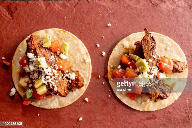 beef carne asada mexican tijuana style street food tacos with marinated steak, cilantro, onion, cotija cheese and sour cream - carne assada imagens e fotografias de stock