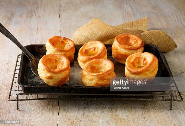 beef dripping yorkshire puddings on metal baking tray and wire rack - cooling rack stock photos and pictures