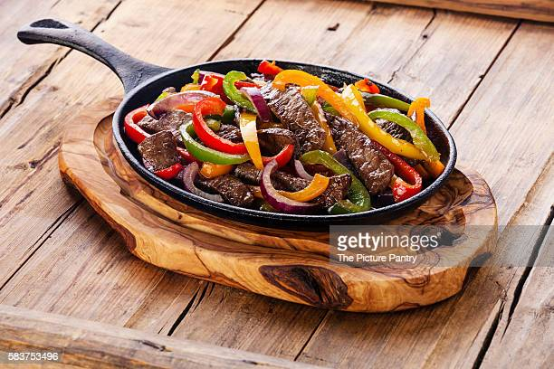 Beef Fajitas with colorful bell peppers in cast iron pan