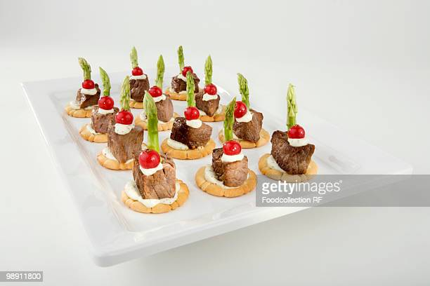 Beef fillet, redcurrants and green asparagus on crackers, close-up