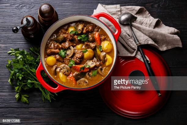 Beef meat stewed with potatoes, carrots and spices in cast iron pan on burned black wooden background
