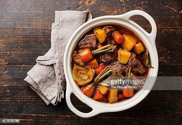 Beef meat stewed with potatoes, carrots and spices in ceramic pot on wooden background