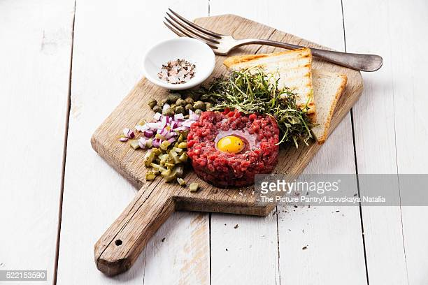 Beef tartare with capers and fresh onion on white wooden backgro