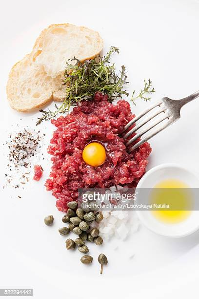 Beef tartare with capers and fresh onions on white background