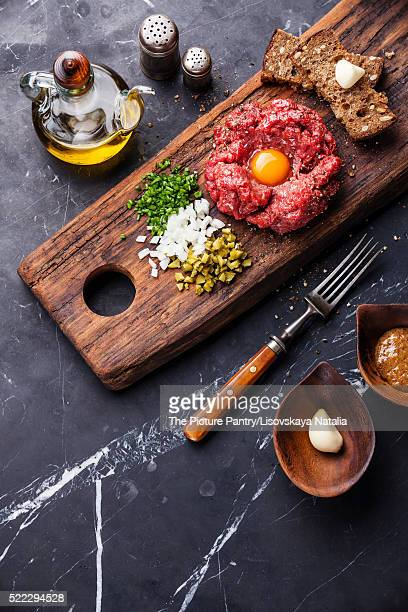 Beef tartare with pickled cucumber and fresh onions on dark marb