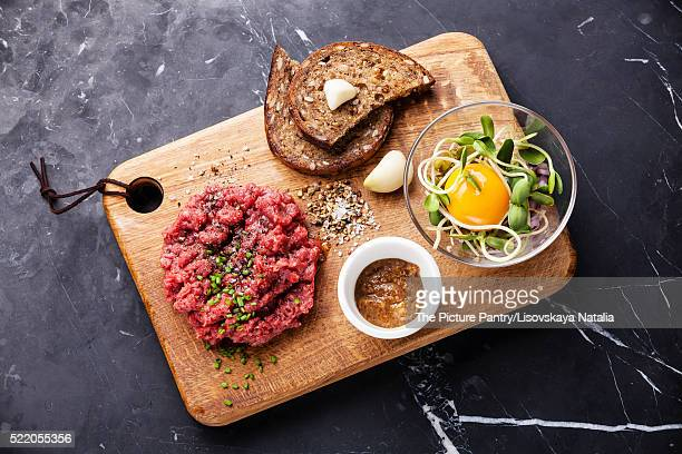 Beef tartare with salad and garlic toasts on dark marble backgro