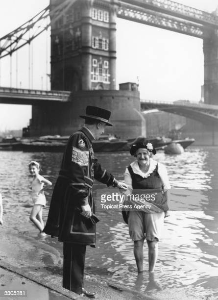 Beefeater from the nearby Tower of London assists a woman paddling in the Thames Tower Bridge is in the background