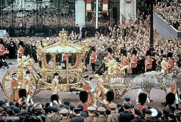 Beefeaters and Royal Guardians walk beside the golden carriage of Queen Elizabeth II during her coronation procession on June 2 1953