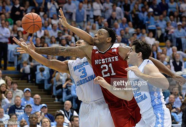 BeeJay Anya of the North Carolina State Wolfpack battles Kennedy Meeks and Luke Maye of the North Carolina Tar Heels for a rebound during their game...