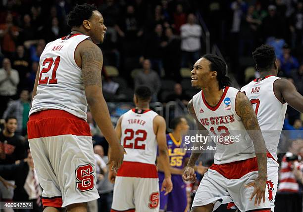 Beejay Anya of the North Carolina State Wolfpack celebrates with teammate Anthony Barber after defeating the LSU Tigers 66 to 65 during the second...