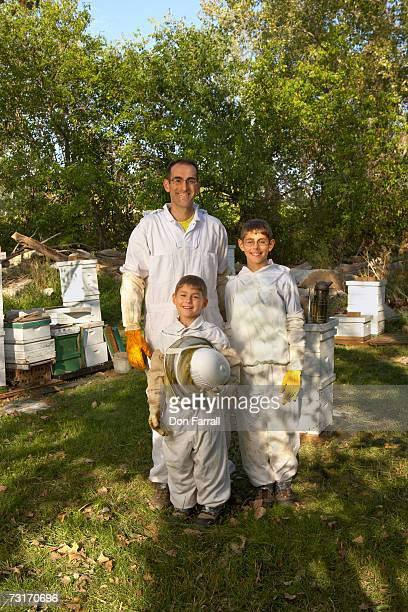 Beekeeper and sons (7-12) standing amongst hives, portrait