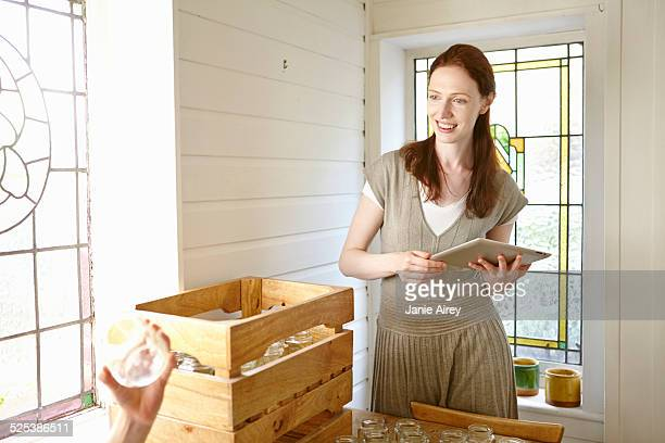 beekeeper using digital tablet in kitchen whilst unpacking jars - 40 44 jaar stock pictures, royalty-free photos & images