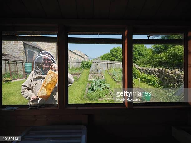 Beekeepers with honey comb in garden