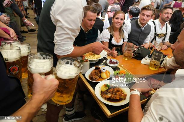 Beer and pork knuckle aarives for revelers celebrating in the Paulaner tent on the opening weekend of the 2019 Oktoberfest on September 21 2019 in...